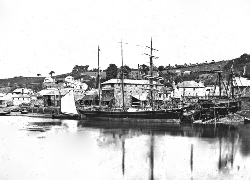 Barquentine Winifred moored alongside Restarick's shipyard, with stores advertising Fison's manures.